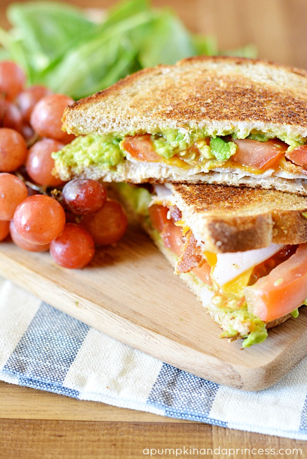 avocado, bacon, turkey sandwich topped with tomatoes and cheddar ...