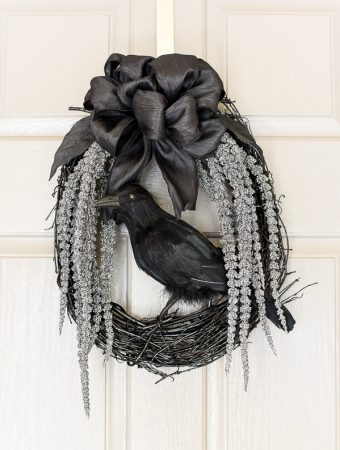 DIY spooky glam Halloween wreath with glittery stems draping down and a black crow to welcome your guests.