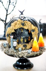Create a Haunted House Pumpkin Diorama with tiny spooky decorations, complete with a skeleton walkway, candy corn trees and tombstones.