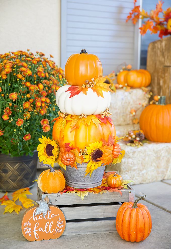 Fall porch pumpkin topiary made with faux pumpkins in a farmhouse metal bucket