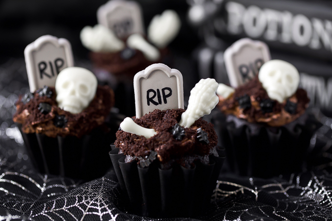 Halloween Cupcakes - chocolate graveyard cupcakes toped with white chocolate bones, cookie crumbs, and a tombstone.