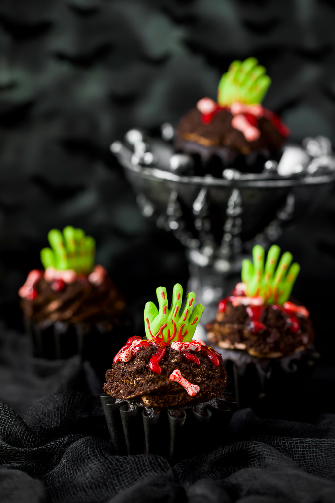 Chocolate cupcakes decorated with green zombie hands and red icing