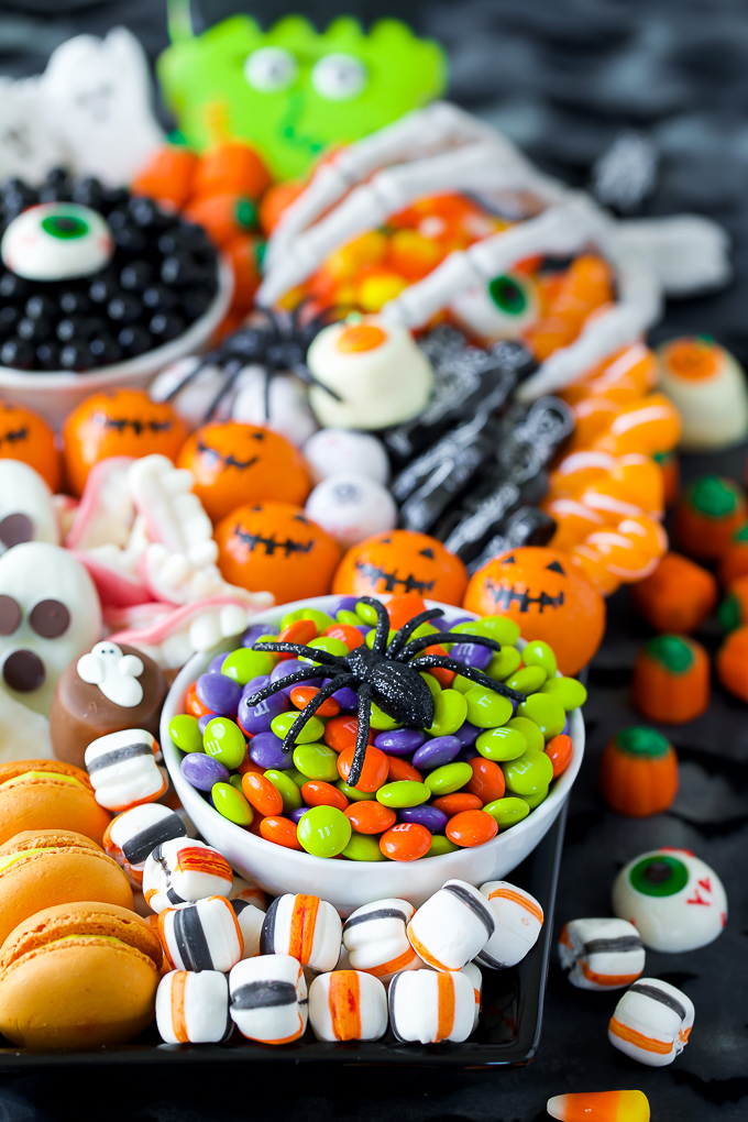 The ultimate Halloween candy board decorated with skeleton hands and spiders
