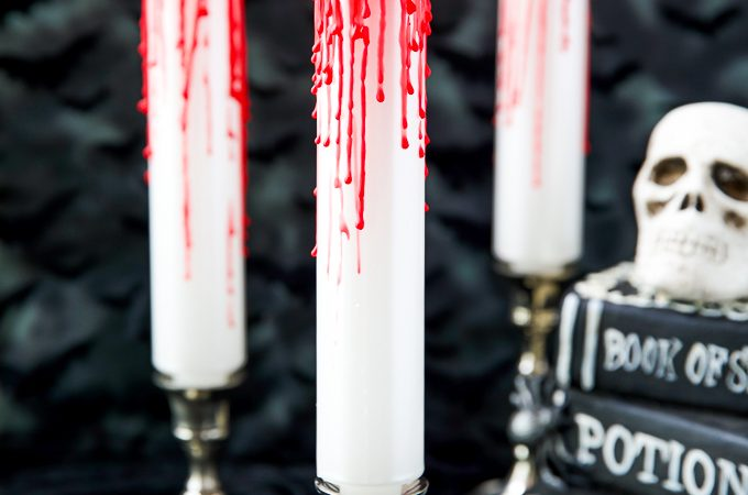 White taper candles with red candle drips - how to make your own bleeding candles for a Halloween table