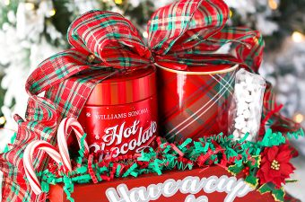 Handmade hot chocolate gift basket made in a wooden crate, filled with a holiday mug, hot cocoa, marshmallows, and candy canes.