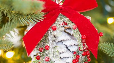 Snow covered pine cone ornament decorated with Christmas greenery and red berries