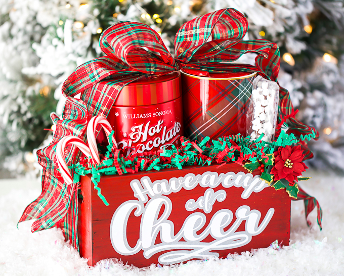 DIY Hot Chocolate Gifts - create a gift basket filled with hot chocolate, a Christmas mug, marshmallows, and candy canes. Wrapped in a beautiful plaid ribbon and glitter vinyl lettering.