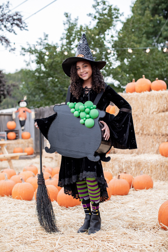 Halloween witch costume with bubbling cauldron
