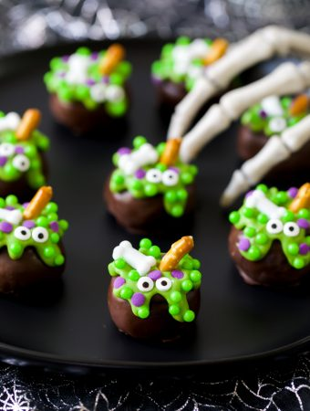 chocolate covered Halloween Cauldron OREO balls decorated with green chocolate, candy eyes, bones, and a pretzel stick