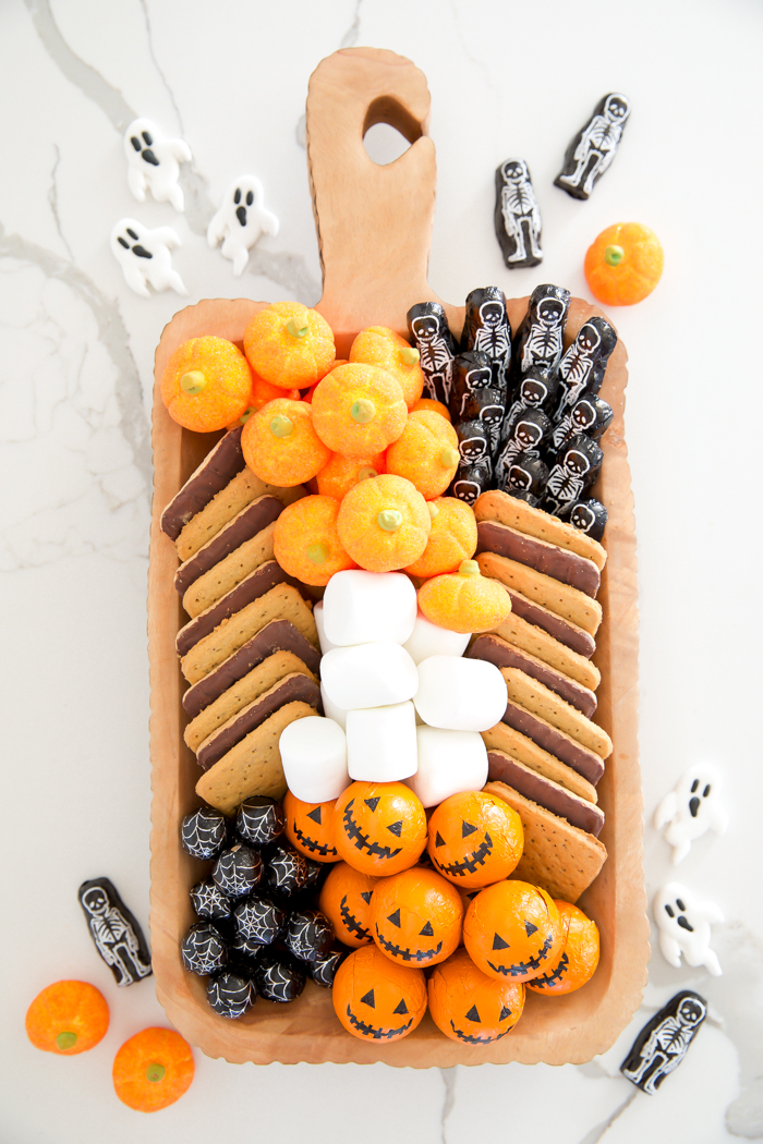 S'mores board ideas for Halloween with pumpkin marshmallows, pumpkin chocolate balls, and skeleton chocolate bars