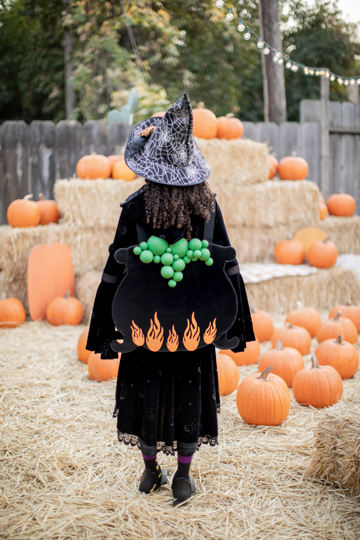 Witch costume with bubbling cauldron and orange fire flames