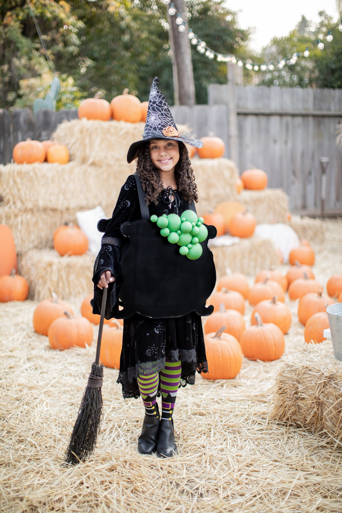 witch costume with striped leggings, bubbling cauldron, and witch hat