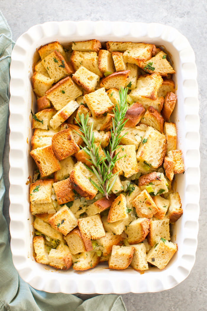 Homemade stuffing recipe made with gluten-free bread cubes, broth, vegetables, and fresh herbs.