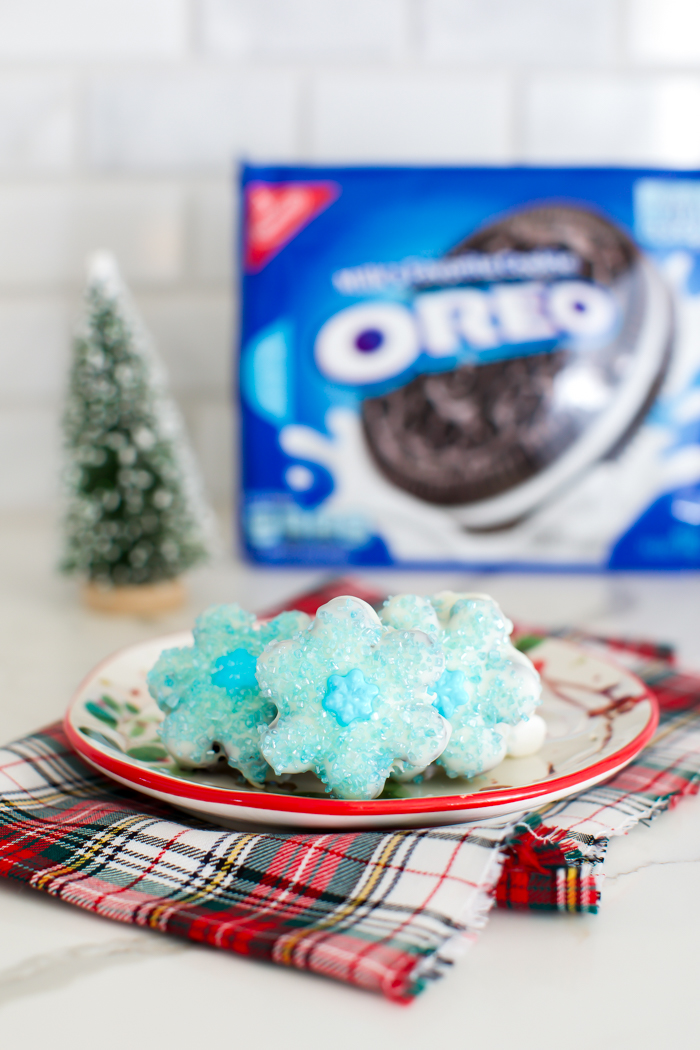 snowflake shaped oreo truffles dipped in white chocolate and decorated with blue sprinkles