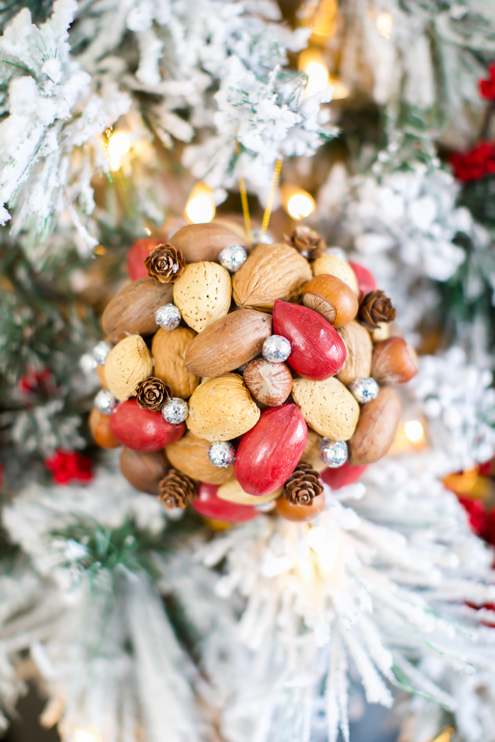 Nature inspired nut ornament craft with red pecans, pinecones, and berries