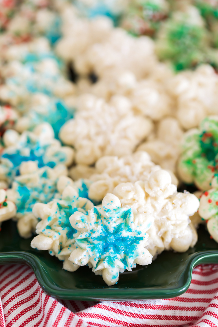 buttery snowflake spritz cookies decorated with blue sprinkles