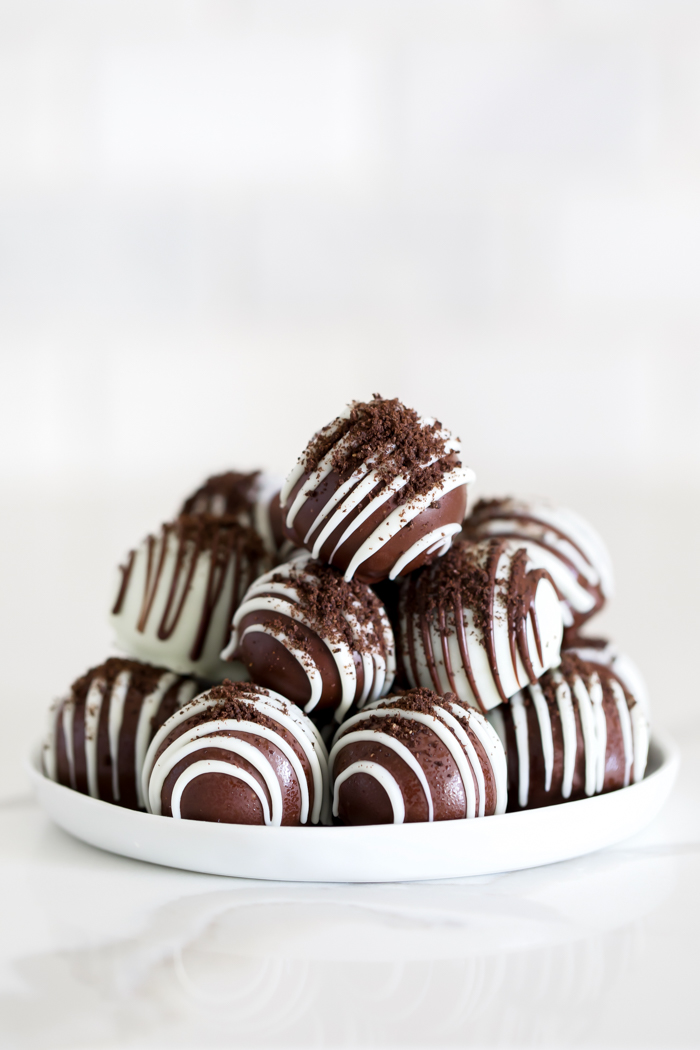 Gluten free Oreo ball recipe dipped in chocolate, with chocolate drizzle, and crushed oreo crumbs
