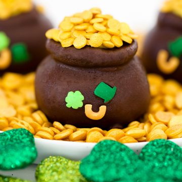 chocolate covered oreo balls shaped into pots of gold with sprinkles
