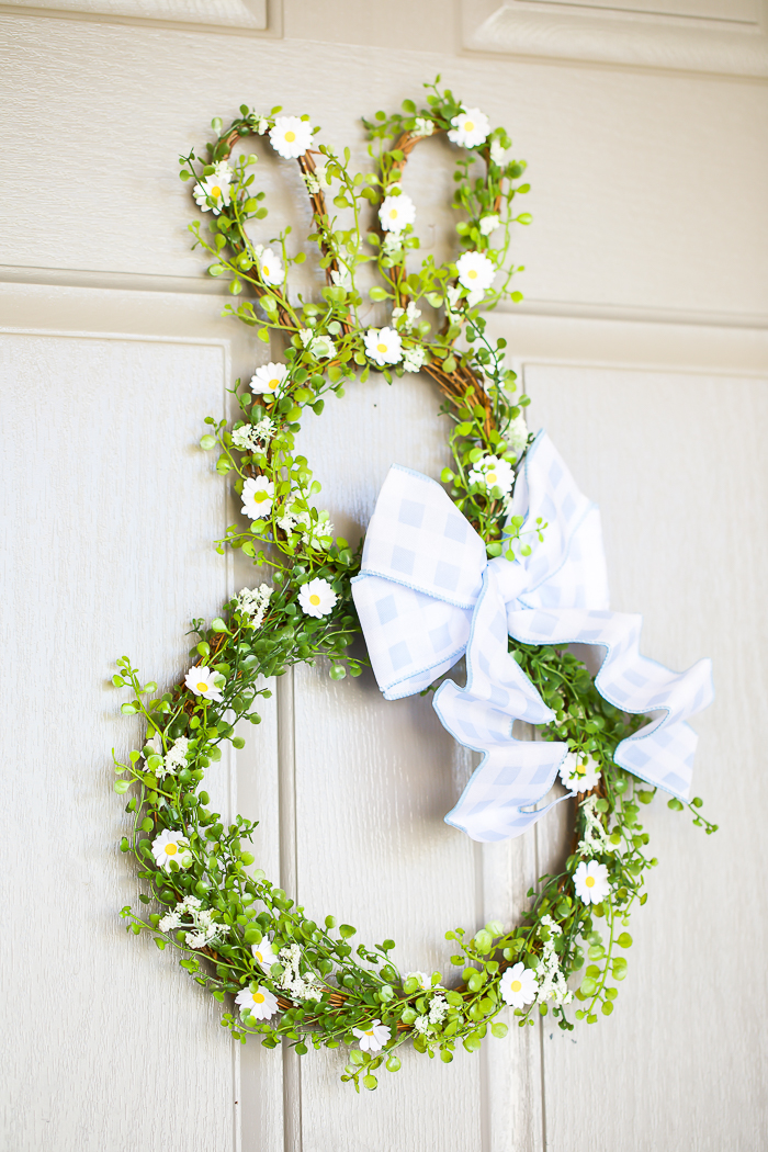 Handmade Easter bunny wreath with greenery, daisy flowers, and a blue gingham bow