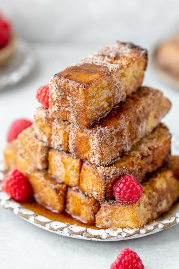 syrup topped french toast sticks and raspberries