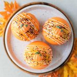 Easy pumpkin spice hot cocoa bombs in an orange chocolate shell with sprinkles